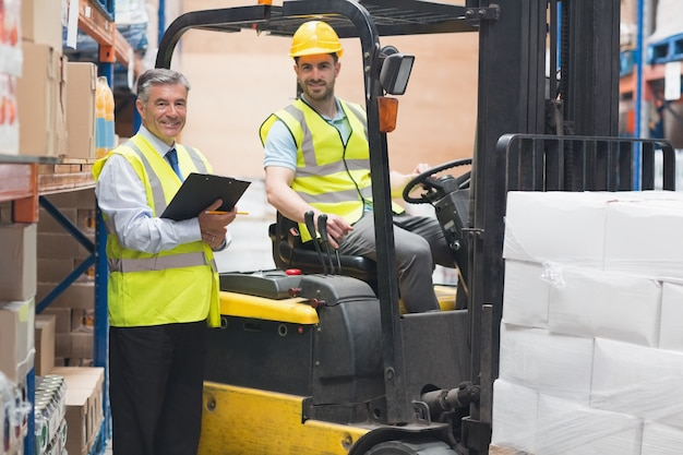 Driver operating forklift machine next to his manager