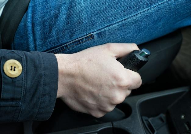 자동차에서 핸드 브레이크를 당기는 드라이버. 안전벨트가 매여 있습니다.