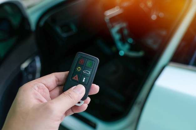 Driver's hand holding car remote control and open the vehicle door with keyless entry system.
