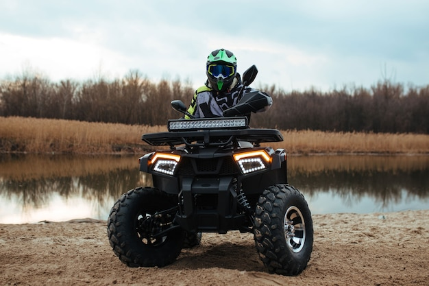 The driver sits on a quad bike nearby the river