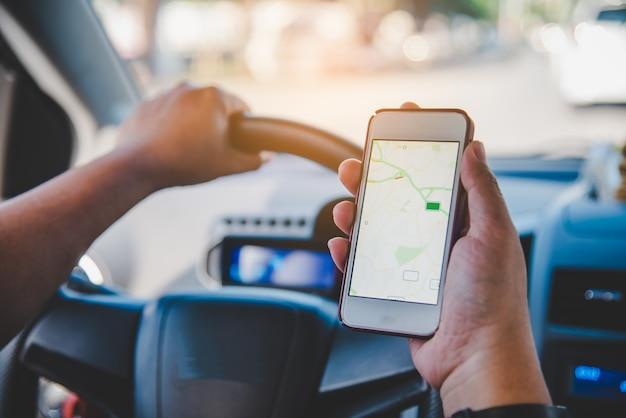 車に座って地図付き携帯スマートフォンを持っているドライバー