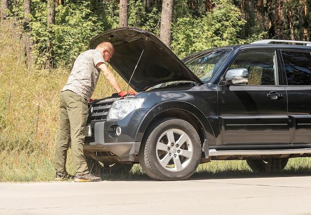 여름 여행에서 자동차 휴식 후 문제로 서서 후드 내부를 바라보는 운전자