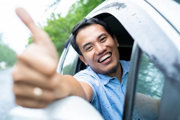 Водитель такси онлайн улыбается и показывает большой палец вверх