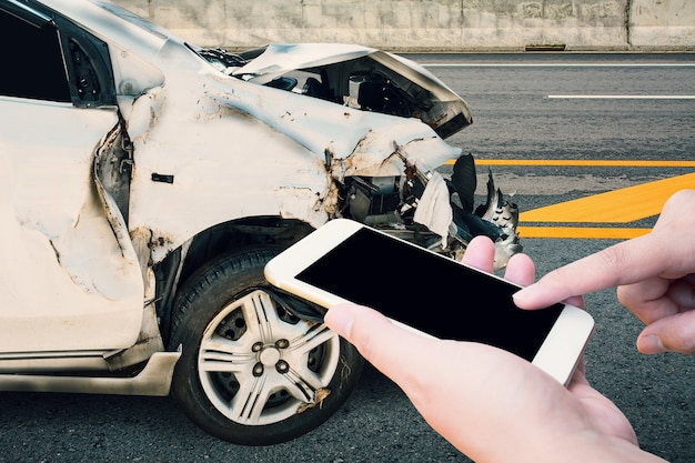 Driver using mobile smartphone with car crash accident on the road