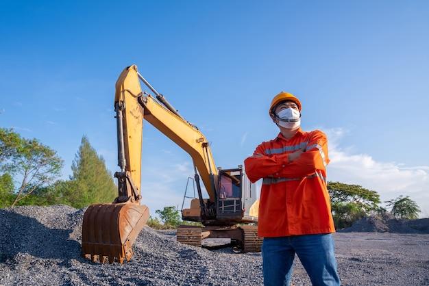 青空の背景に彼の後ろの建設現場を掘るクローラーショベルを持つドライバー