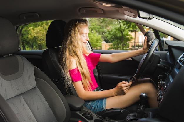 車の中でスマートフォンを持っているドライバー