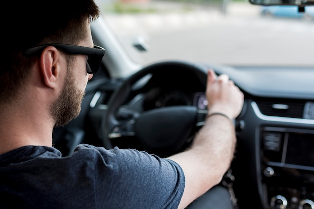 Driver with sunglasses holding steering wheel