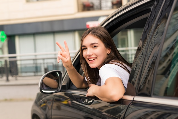 Driver woman of car waves back as sign of farewell on the street
