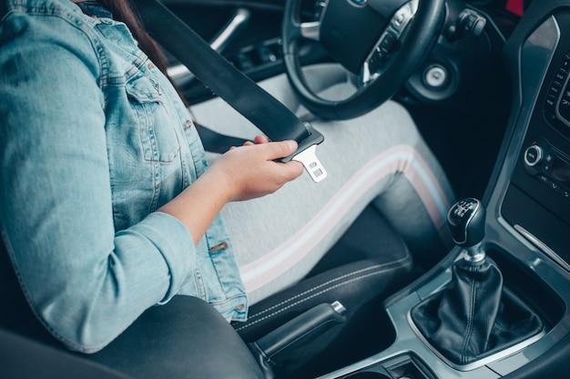 車の衝突、安全コンセプト、安全な輸送に対して、車の中でシートベルトを締めるドライバーの女性