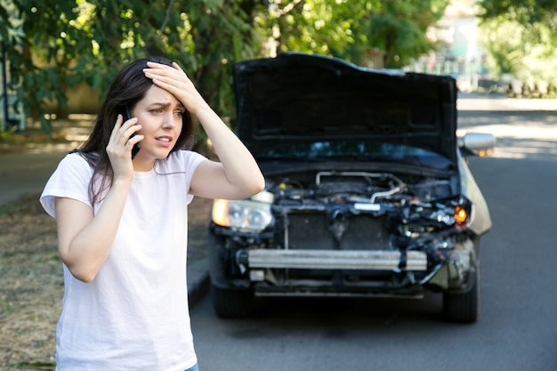 Driver woman in front of wrecked car in car accident. scared woman in stress holding her head after auto crash calling to auto insurance for help. dangerous road traffic situation.