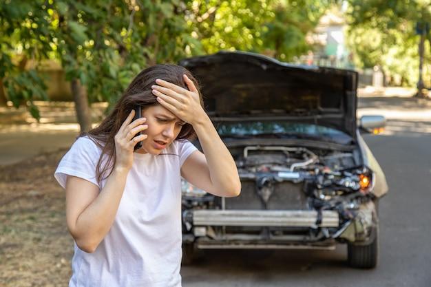 교통사고로 난파된 차 앞의 운전사 여성 초상화. 자동차 보험에 도움을 요청하는 자동차 사고 후 스트레스를 받고 있는 겁에 질린 여성. 위험한 도로 교통 상황.