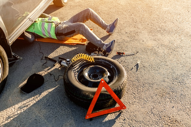 A driver or worker repairs a broken car on the side of the road. view from above. man is under the car