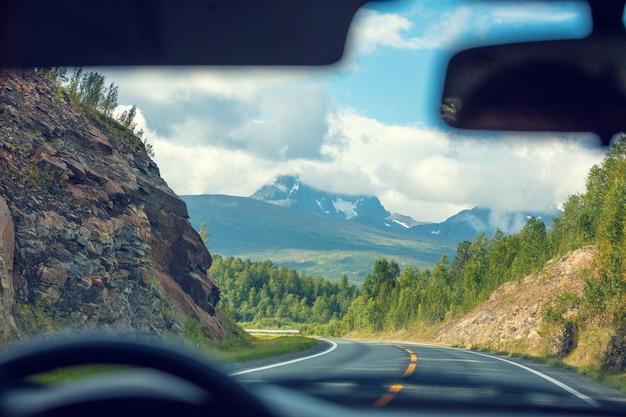 山道で車を運転する。山の間の道。ノルウェーの美しい自然
