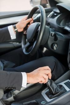 За рулем новой машины. крупный план человека в формальной одежде за рулем автомобиля