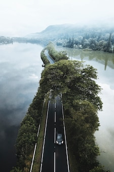 Driving along the road on a lake drone shot