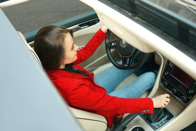 도시 주변을 운전. 차를 운전하는 젊은 매력적인 여자. 현대적인 차량 내부에 앉아 있는 우아하고 세련된 빨간 재킷을 입은 젊은 백인 모델. 사업가 개념입니다. 인간의 감정 개념