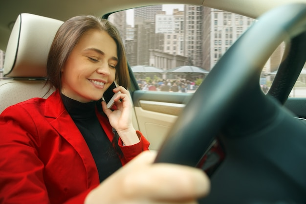 街中を運転。車を運転する若い魅力的な女性。モダンな車のインテリアに座っているエレガントでスタイリッシュな赤いジャケットの若いかわいい白人モデル。実業家の概念。