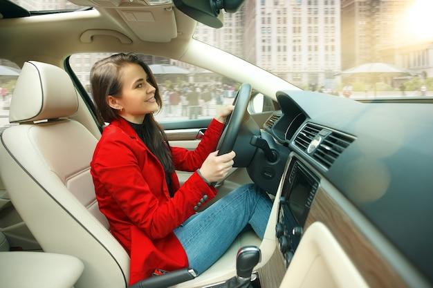 도시 주변을 운전합니다. 차를 운전하는 젊은 매력적인 여자. 현대 차량 내부에 앉아 우아한 세련된 빨간 재킷에 젊은 꽤 백인 모델
