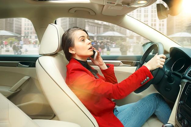 Езда по городу. молодая привлекательная женщина за рулем автомобиля. молодая симпатичная кавказская модель в элегантной стильной красной куртке сидит в интерьере современного автомобиля