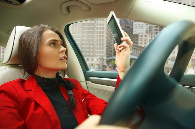 街中を運転。車を運転する若い魅力的な女性