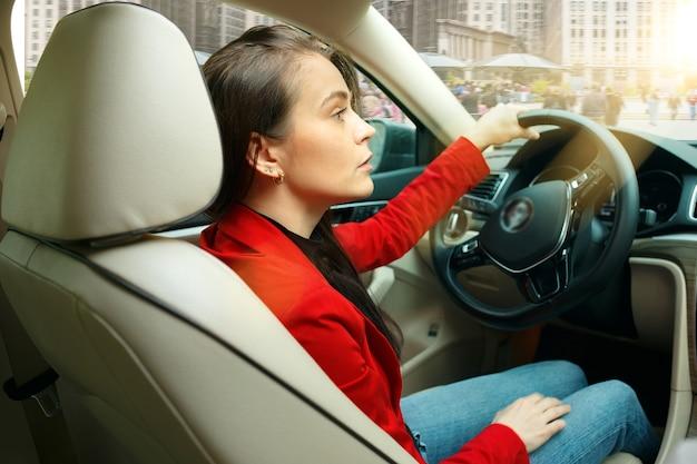 도시 주변을 운전합니다. 차를 운전하는 젊은 매력적인 여자