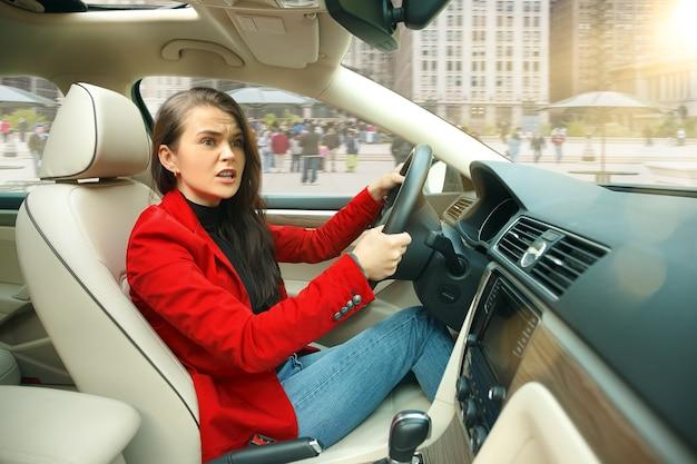 도시 주변을 운전합니다. 차를 운전하는 젊은 매력적인 여자.