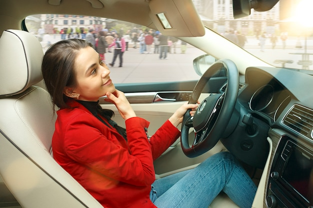 Driving around city. young attractive woman driving a car. young pretty caucasian model in elegant stylish red jacket sitting at modern vehicle interior. businesswoman concept.