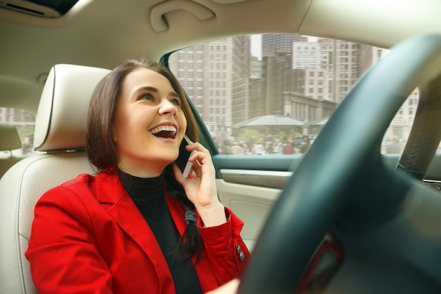 Guidare in città. giovane donna attraente alla guida di un'auto. giovane modello abbastanza caucasico in elegante giacca rossa alla moda che si siede all'interno del veicolo moderno