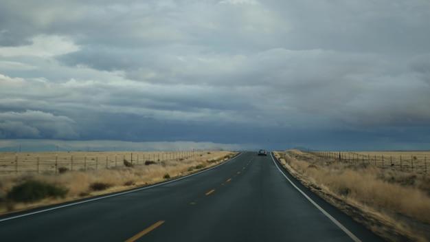 자동차 운전, 미국 캘리포니아의 도로 여행, 차에서 봅니다. 미국을 여행하는 히치하이킹. 비 폭풍 전에 고속도로, 산 및 흐린 극적인 하늘. 미국의 경치 좋은 샛길. 승객 관점.