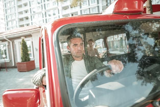 침착하게 운전. 뒷좌석에 앉아 있는 승객을 시내로 데려가는 심각한 자동차 운전사.
