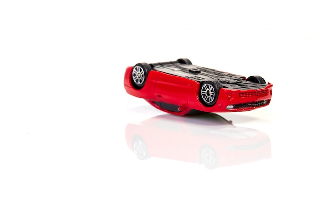 Driving car in alcoholic intoxication: red toy car lies upside down on white