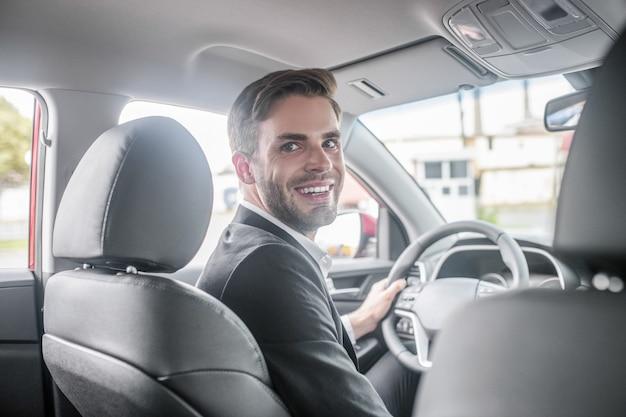 Вождение машины. счастливый молодой взрослый человек в темном деловом костюме за рулем автомобиля, держа руль, поворачивая голову назад