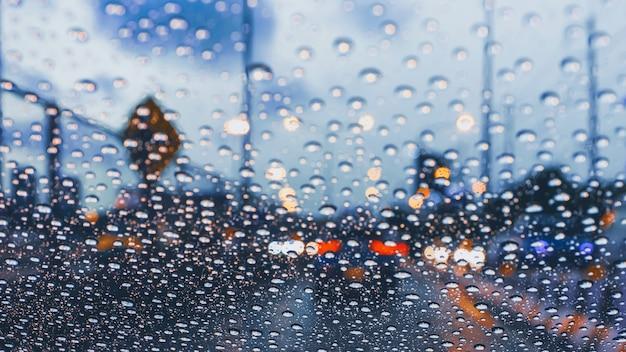 風防の上に雨滴が付いている交通渋滞で大都市の道路で車を運転
