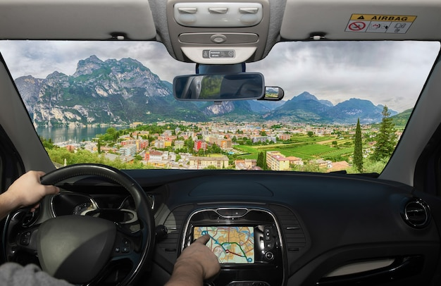 Driving a car while using the touch screen of a gps navigation system towards riva del garda, northern lake garda, trento, italy