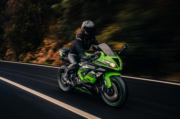За рулем зеленого мотоцикла по дороге.