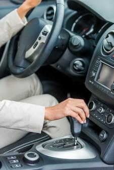 За рулем своей новой машины. крупный план женщины в формальной одежде за рулем автомобиля