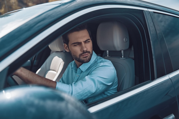 За рулем своей новенькой машины. красивый молодой человек в элегантной повседневной одежде смотрит в сторону за рулем статусного автомобиля
