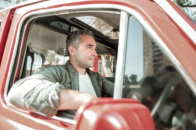 집에 운전. 잘생긴 남자가 창밖으로 팔꿈치를 내밀고 있는 빨간 차의 운전대에 앉아 웃고 있습니다.