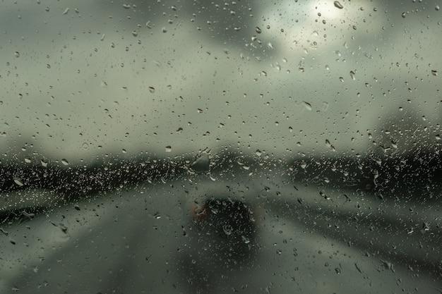 비에서 운전. 자동차 유리 표면에 비가 떨어집니다. 비가 오는 날에 추상 트래픽. 카시트에서 봅니다. 비 방울, 선택적 포커스와 차 창을 통해도보기.