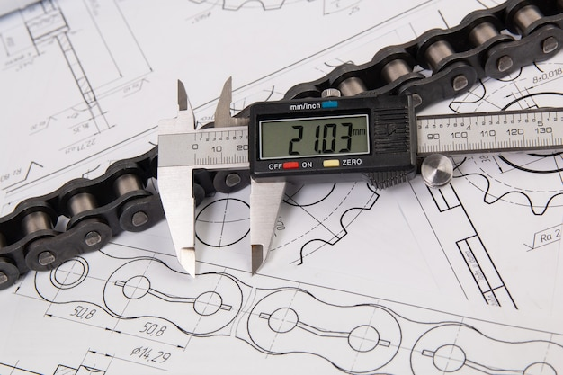 Driving industrial roller chain and digital caliper on a print engineering drawings