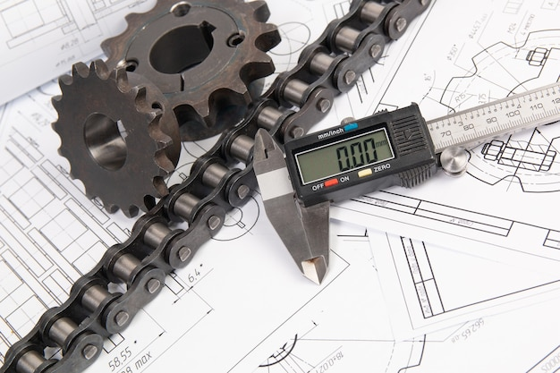 Driving industrial roller chain, digital caliper and sprocket on a print engineering drawings