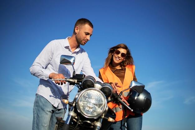 Инструктор по вождению показывает команды мотоцикла и приборную панель неопытному студенту.