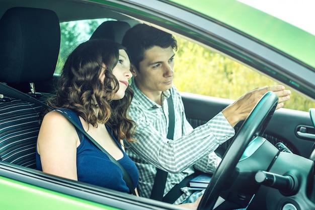 Инструктор по вождению обучает женщину вождению в машине