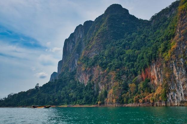 美しい岩の多い風景の中のタイのカオソック湖でロングテールボートを運転