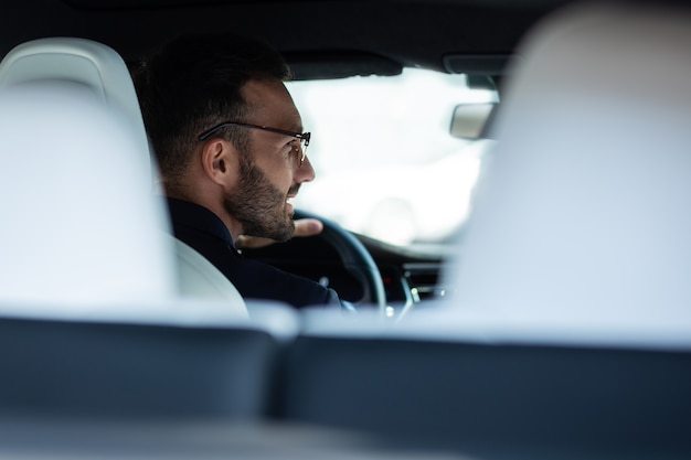 責任を持って運転する。責任を持って運転しながらサイドミラーを見ているひげを生やしたハンサムな若い男