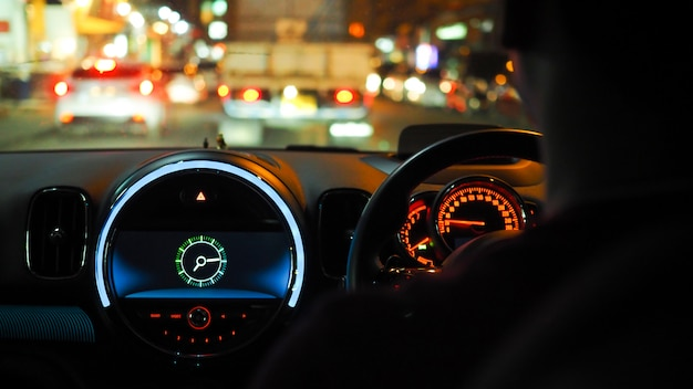Driving on the road at night inside car on the control panel