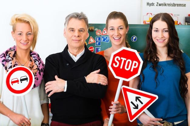 Автошкола - инструктор по вождению и студенты-водители смотрят на дорожный знак темп тридцать