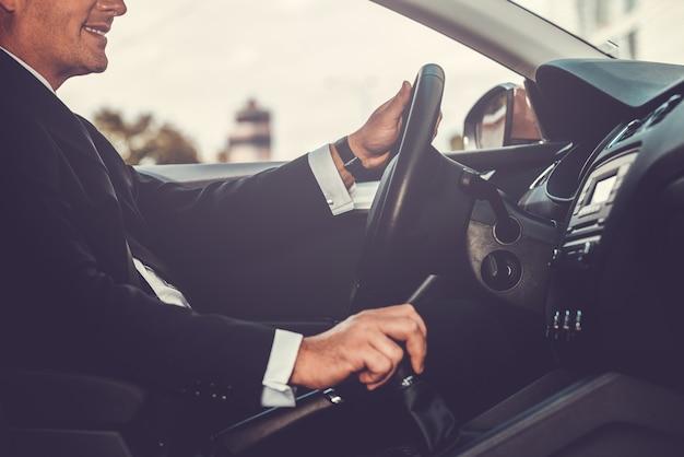 Вождение с комфортом. крупным планом веселый зрелый мужчина в формальной одежде за рулем автомобиля и улыбается