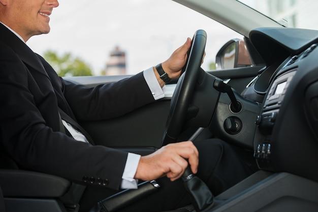 편안한 운전. 차를 운전하고 웃는 formalwear에서 쾌활한 성숙한 남자의 근접