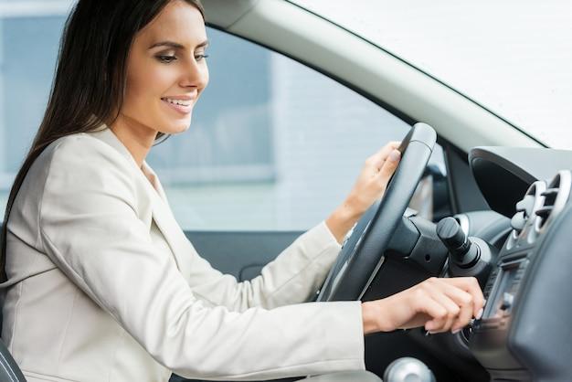 Комфортное вождение. вид сбоку красивого молодого человека в формальной одежде за рулем автомобиля и касания приборной панели пальцем